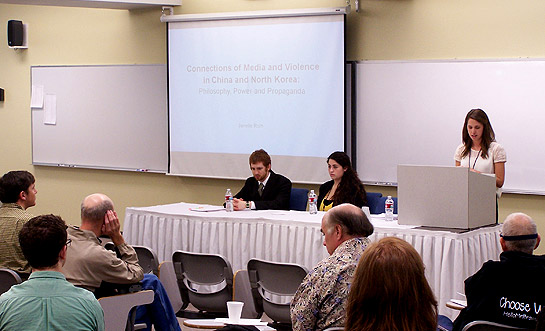 Janelle Roth, right, gives her presentation. Seated are student presenters Stephen Lennstrom and Jiovanna Aguirre-Smith