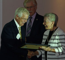Dr. Betty Dean presents Lou Gerard with a certificate, while Maurice Johannessen looks on