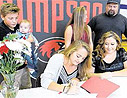 Kelsie Jurin signing her letter of intent to play basketball at Simpson
